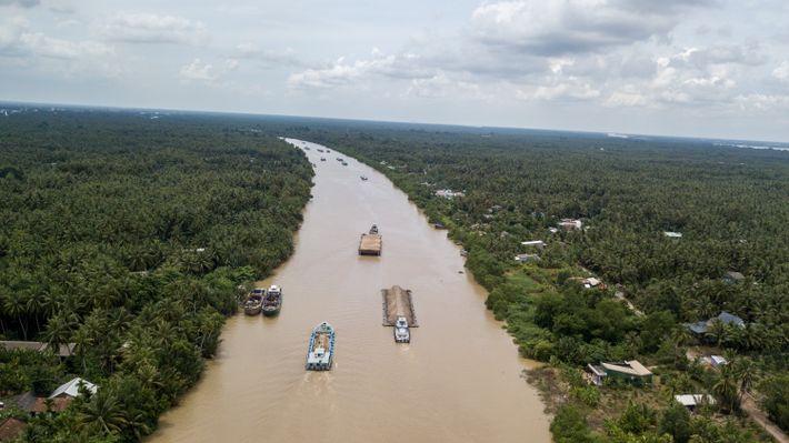 Las barcazas de arena se detienen en el canal Cho Gao en la ruta hacia la ...