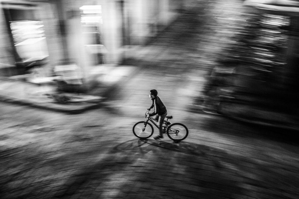 Un joven conduce una bicicleta en la noche llevando una máscara sobre su rostro durante la ...