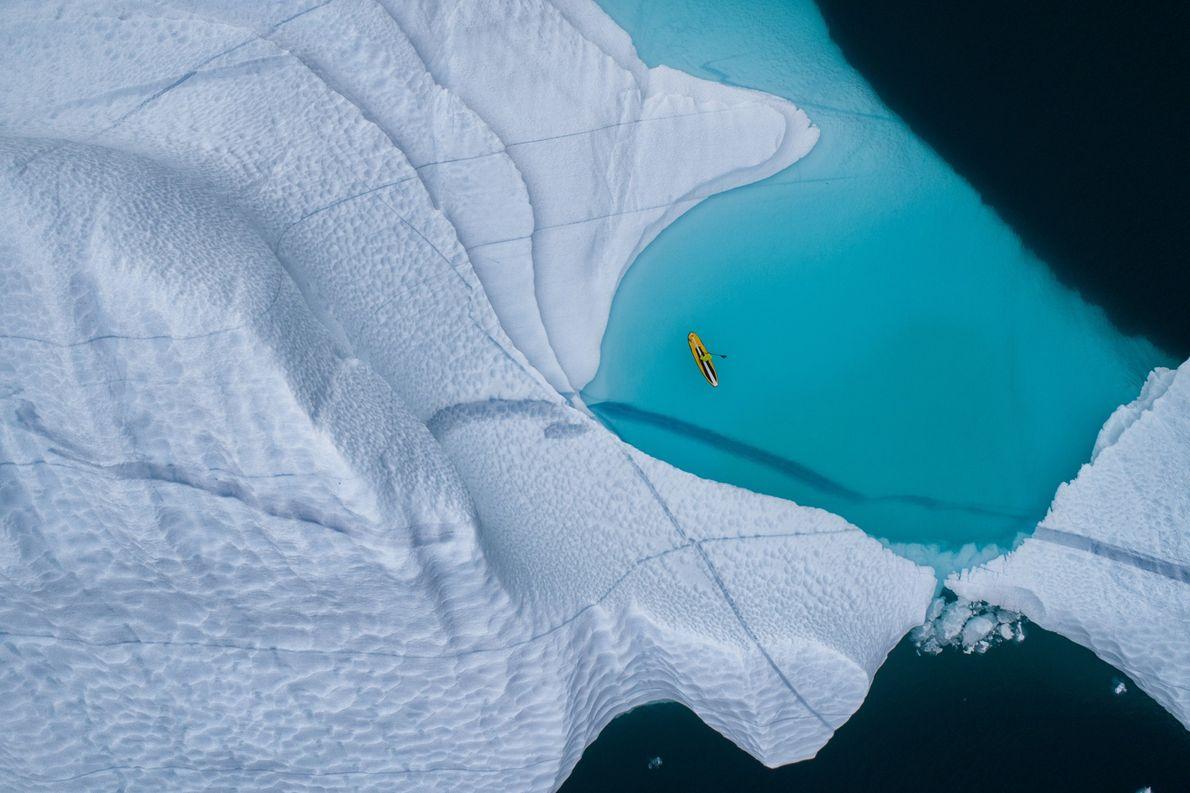 """Un """"paddleboarder"""" de pie atraviesa las frías aguas del mar de Groenlandia."""
