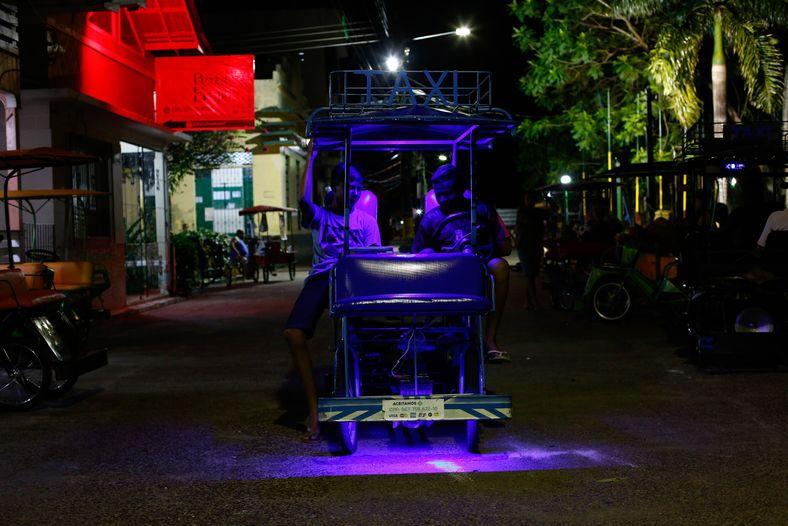 Los conductores de los bicitaxis esperan a los clientes en la costa de la ciudad. Según ...