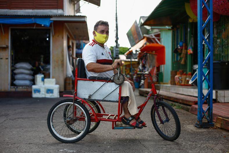 El agente administrativo Irlan Ferreira Bezerra en su bicicleta adaptada para pedalear con el brazo.