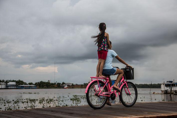 Una niña viaja de pie sobre la grupa, sujetando los hombros del que pedalea, una escena ...