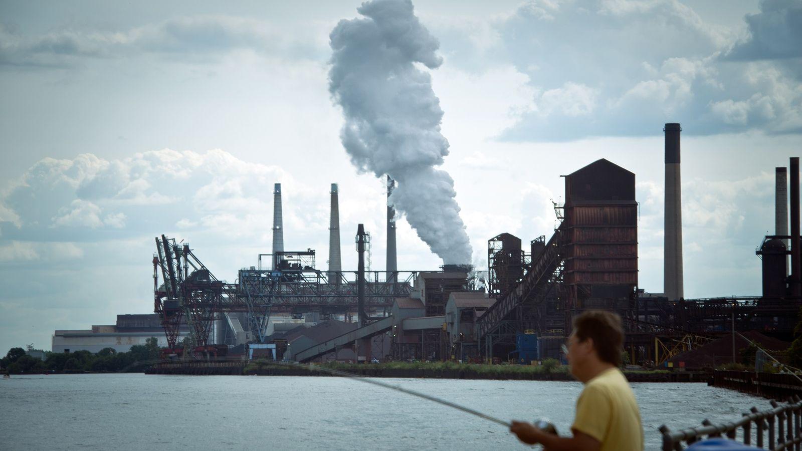 Un hombre pesca cerca de una central de carbón de DTE en Detroit.