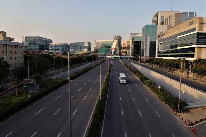 Un solo autobús pasa por una autopista generalmente concurrida en las afueras de Nueva Delhi, India, ...
