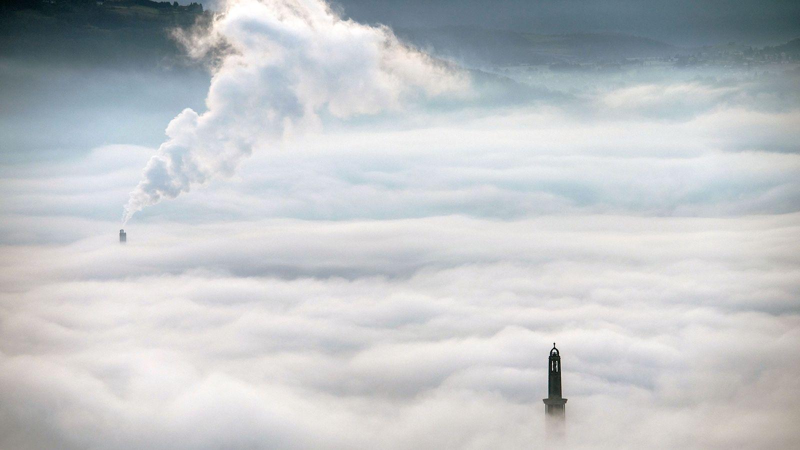 El humo de la planta de calefacción urbana se eleva por encima de las nubes cerca ...