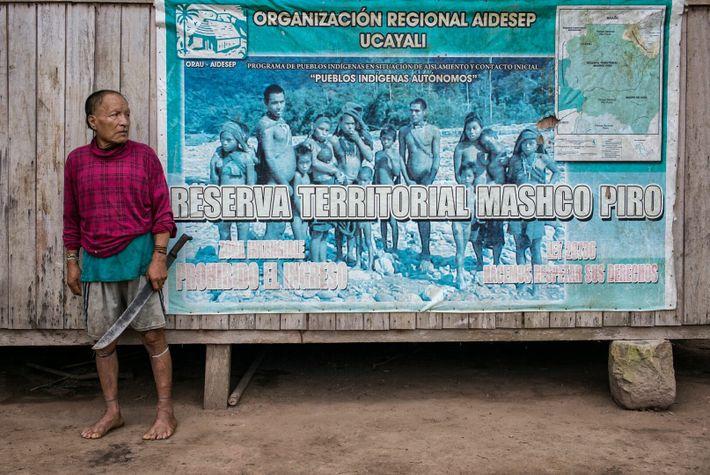Shuri frente a un letrero que indica el puesto de control de la Reserva Indígena mashco ...