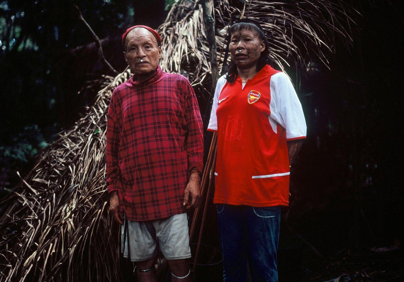 Shuri y su mujer Janet frente a su maloca, una vivienda con tejado de palmas, en ...