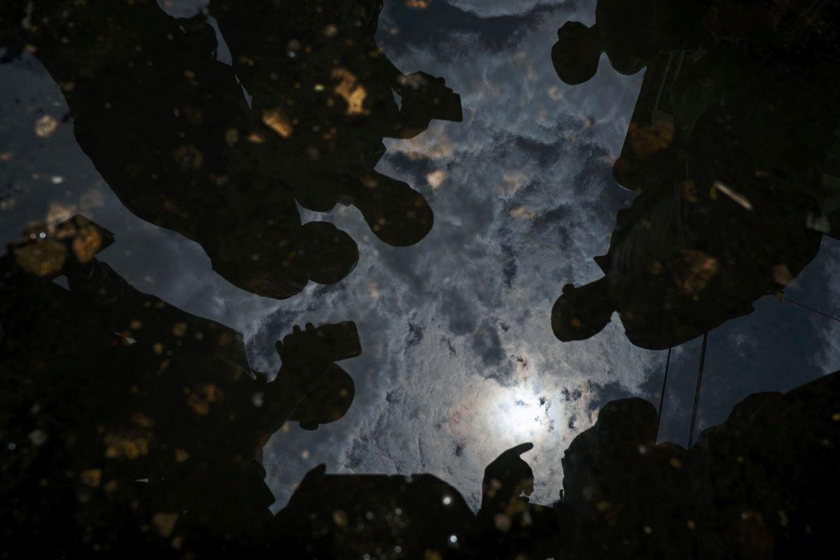 Un eclipse solar anular se refleja en un charco de agua en Tanzania en 2016.