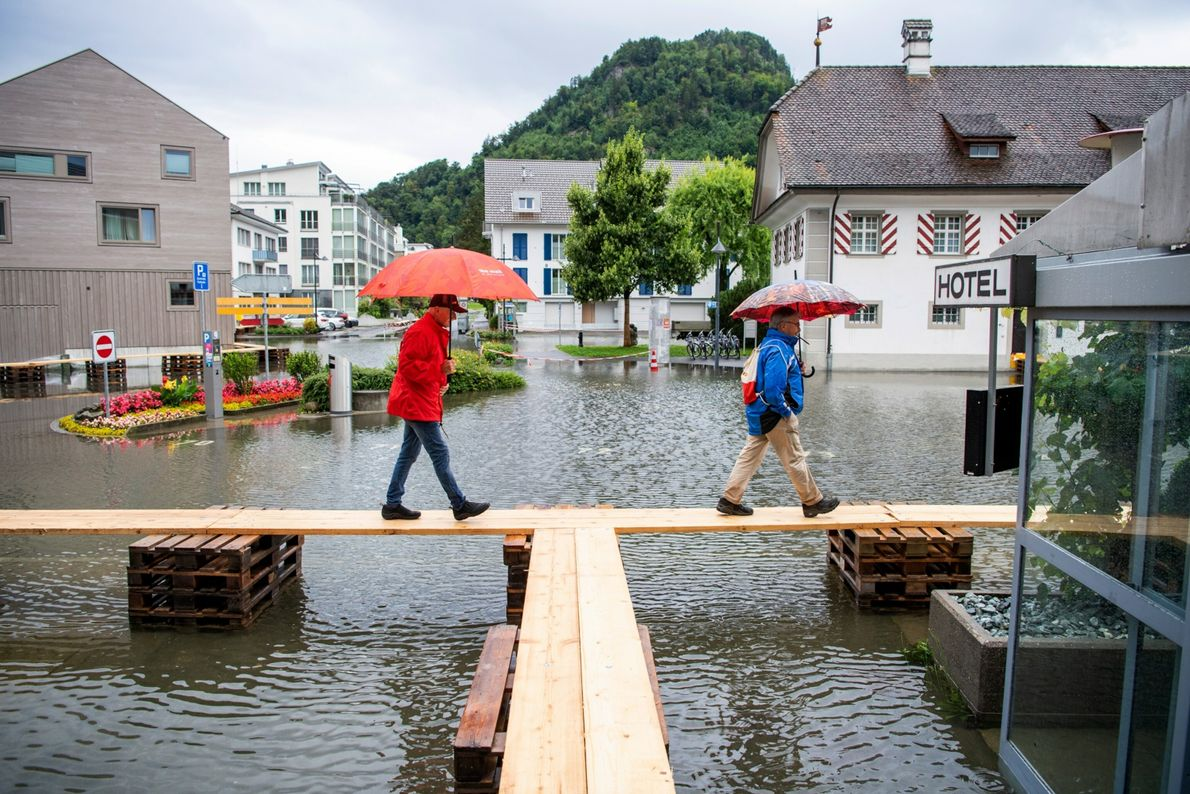 En Suiza, la gente camina por pasarelas para atravesar la plaza inundada.