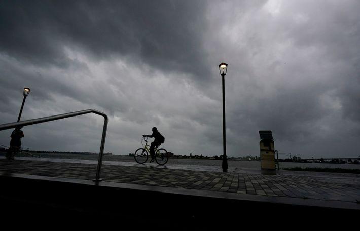 Un hombre anda en bicicleta a lo largo del río Mississippi cerca del Barrio Francés cuando ...