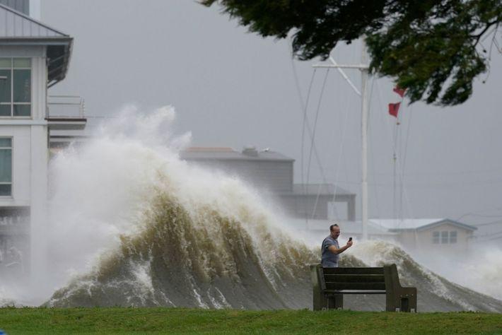 Un hombre usa su teléfono celular para tomar fotografías de las olas altas a lo largo ...