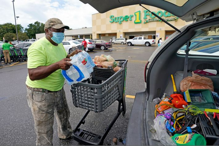 Terry Shelvin carga una caja de agua y comida en su auto en Lafayette, Luisiana, cuando ...