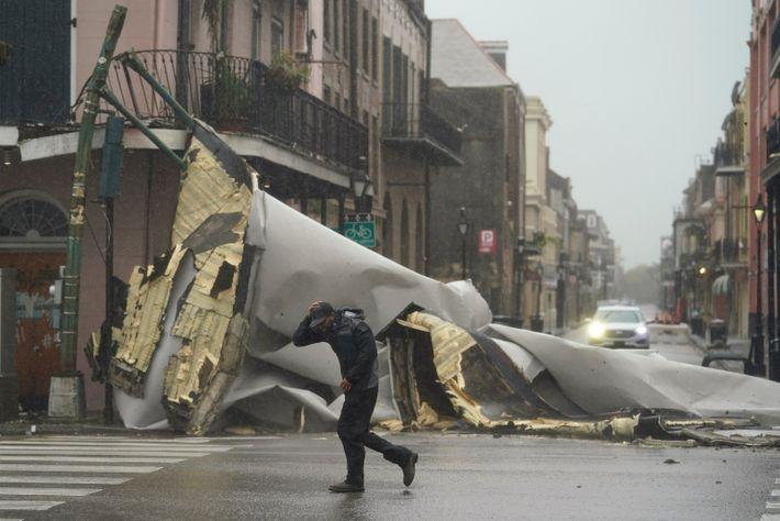 Un hombre pasa por una sección del techo que se desprendió de un edificio por el ...
