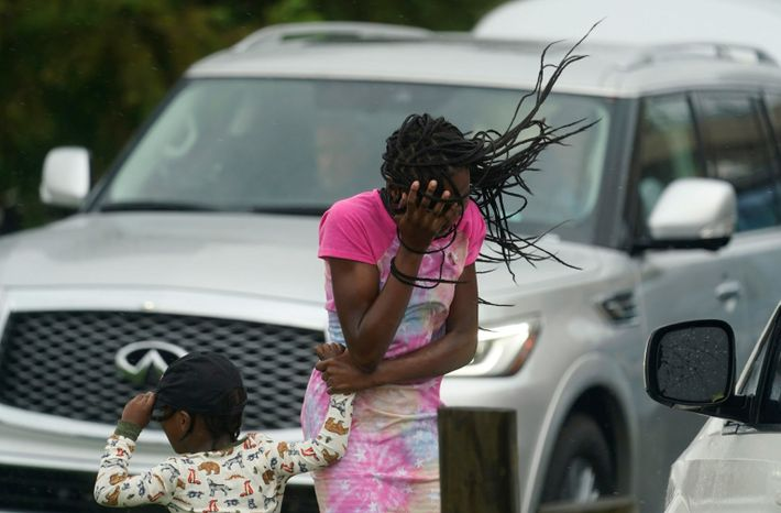 Una niña se tapa su rostro del viento y la lluvia producidos por el huracán Ida ...