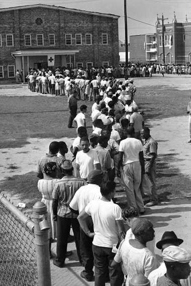 Los refugiados del huracán Betsy esperan en una larga fila para solicitar los beneficios de ayuda ...