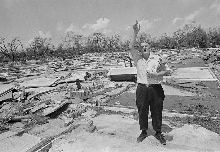 Earl B. Mathews sostiene a su perro en medio de las ruinas de su edificio de ...