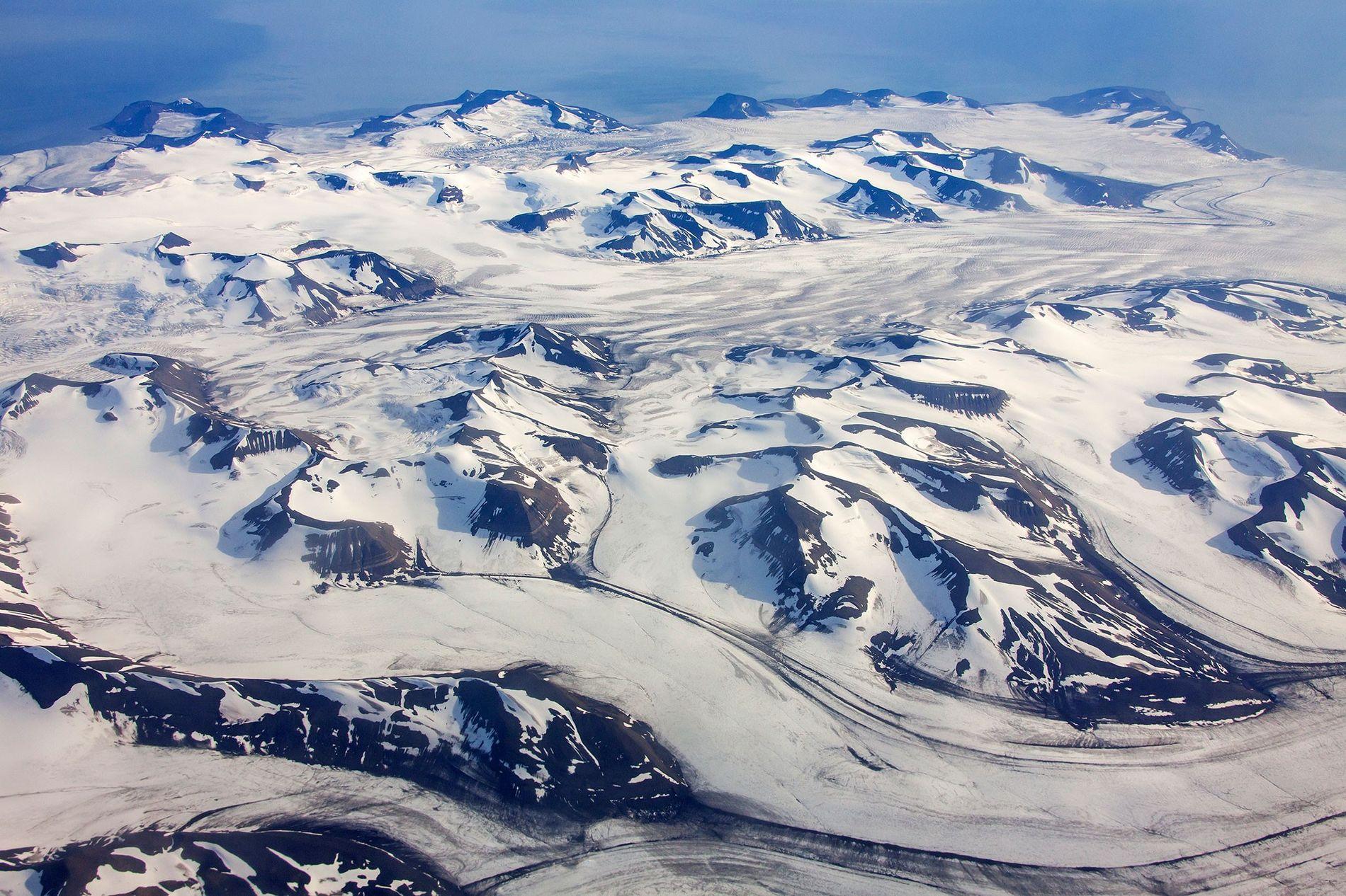 Esta es una vista aérea de un montañoso paisaje de glaciares en Noruega que podría contener ...