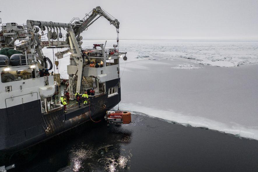 Desde el Kronprins Haakon, hacen descender al vehículo color naranja brillante llamado Neriud Under Ice hacia ...