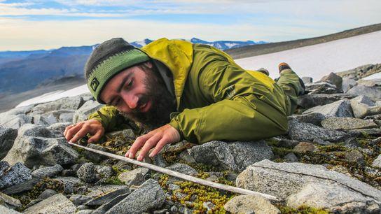 Un investigador examina el astil de una flecha de madera que apareció en el manchón de hielo ...