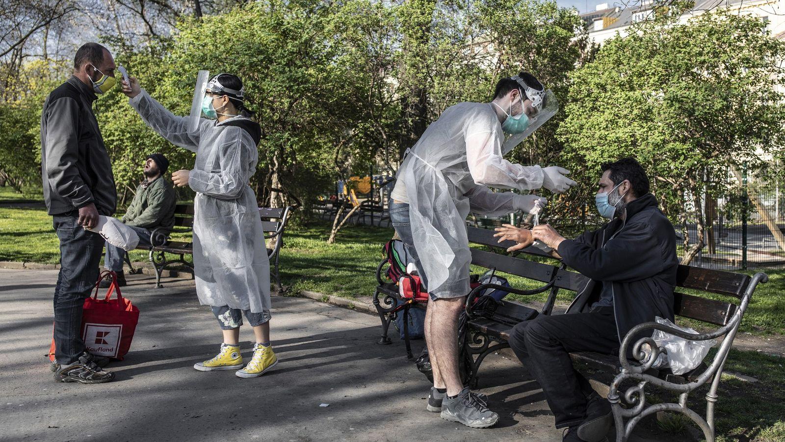 Estudiantes de medicina atienden a personas sin hogar en un parque en Praga durante la pandemia ...
