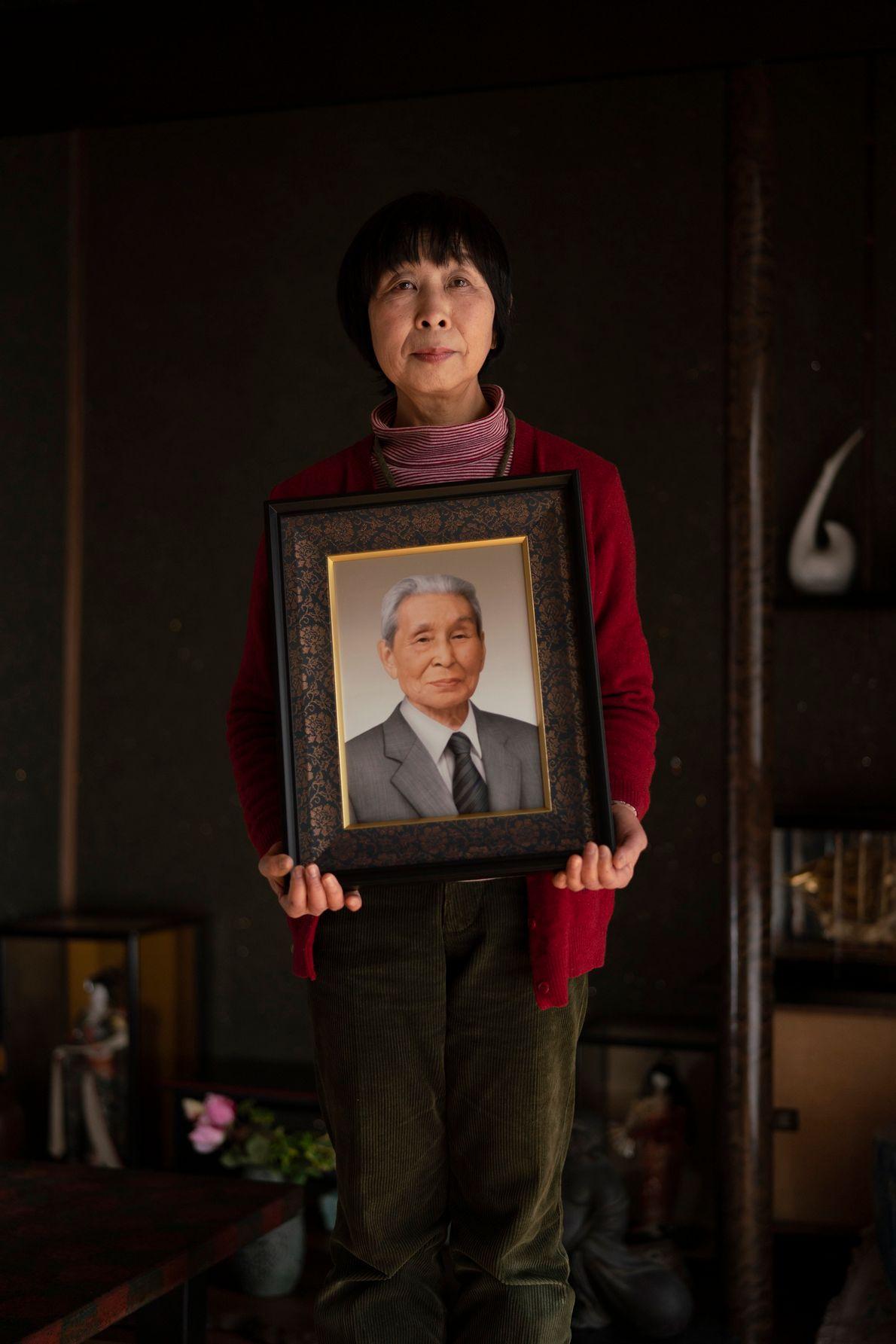 Akiko Funatsu sostiene un retrato de su difunto padre, quien tenía 19 años en el momento ...