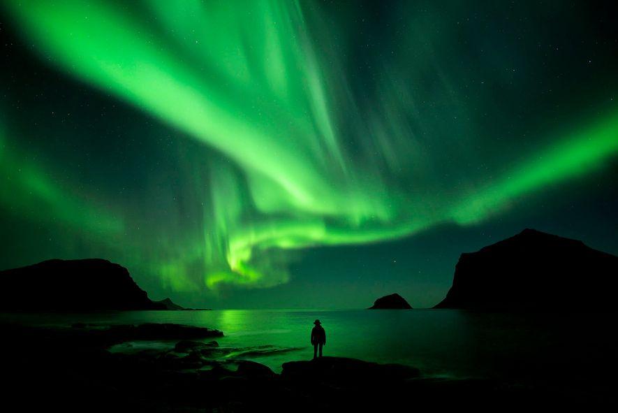 Una mujer contempla las luces de la aurora boreal desde Noruega.