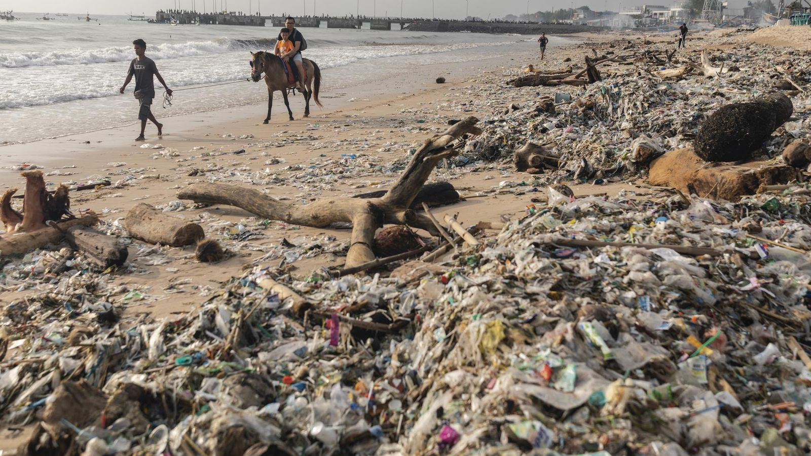 Turistas pasean a caballo por la playa de Kedonganan, Bali, el 27 de enero de 2019. ...