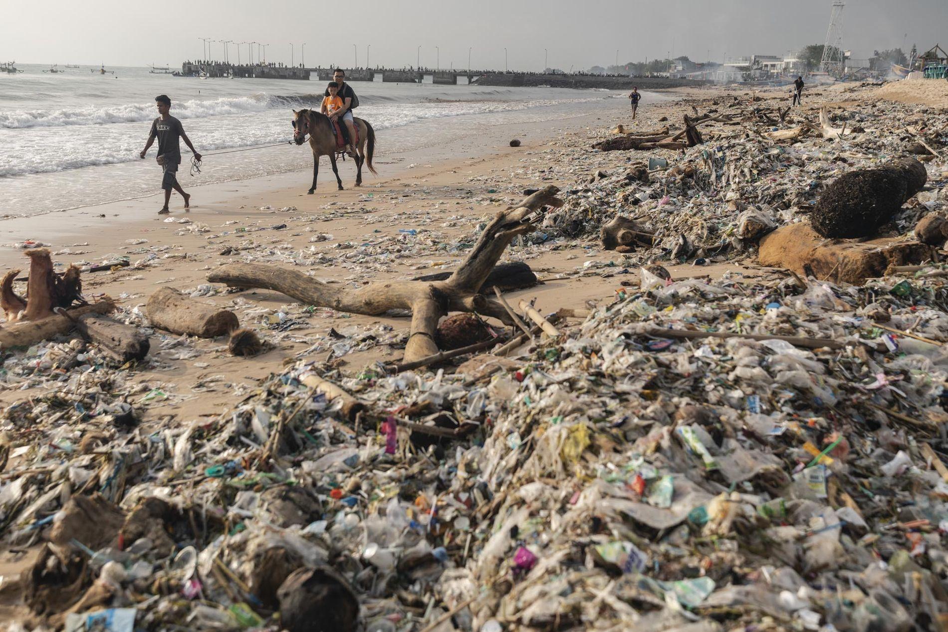 """Turistas pasean a caballo por la playa de Kedonganan, Bali, el 27 de enero de 2019. Todos los años, durante la temporada de lluvias, de noviembre a marzo, llegan toneladas de desperdicios hasta la orilla, por lo que la temporada recibe el apodo de """"temporada de basura""""."""