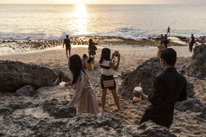 A menudo, los visitantes traen comida a la playa de Tegal Wangi para disfrutar del atardecer, ...