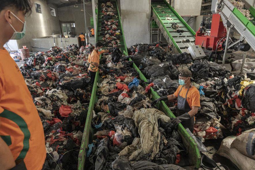 Los trabajadores cargan plástico que será lavado y destruido en el centro de reciclaje Re>Pal en Pasuruan, Java Oriental. Las instalaciones reciclan bolsas de plástico, envoltorios de plástico y algunos envases alimentarios y los convierten en palés que pueden sostener hasta una tonelada.