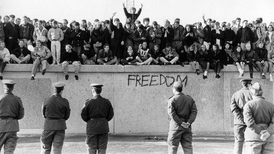 Los alemanes occidentales escalan el Muro de Berlín delante de los guardias de Alemania Oriental mientras ...