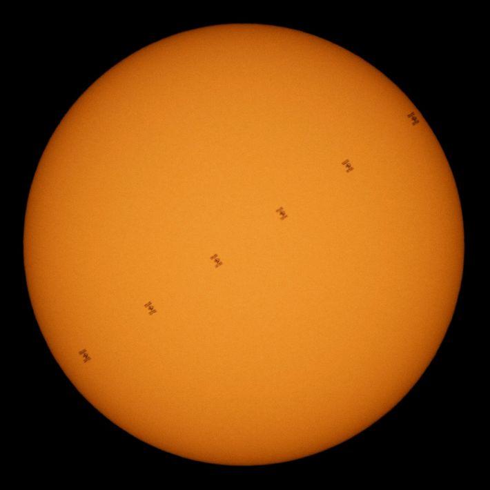 Una línea de puntos negros delante de una esfera brillante: la Estación Espacial Internacional viaja por el ...