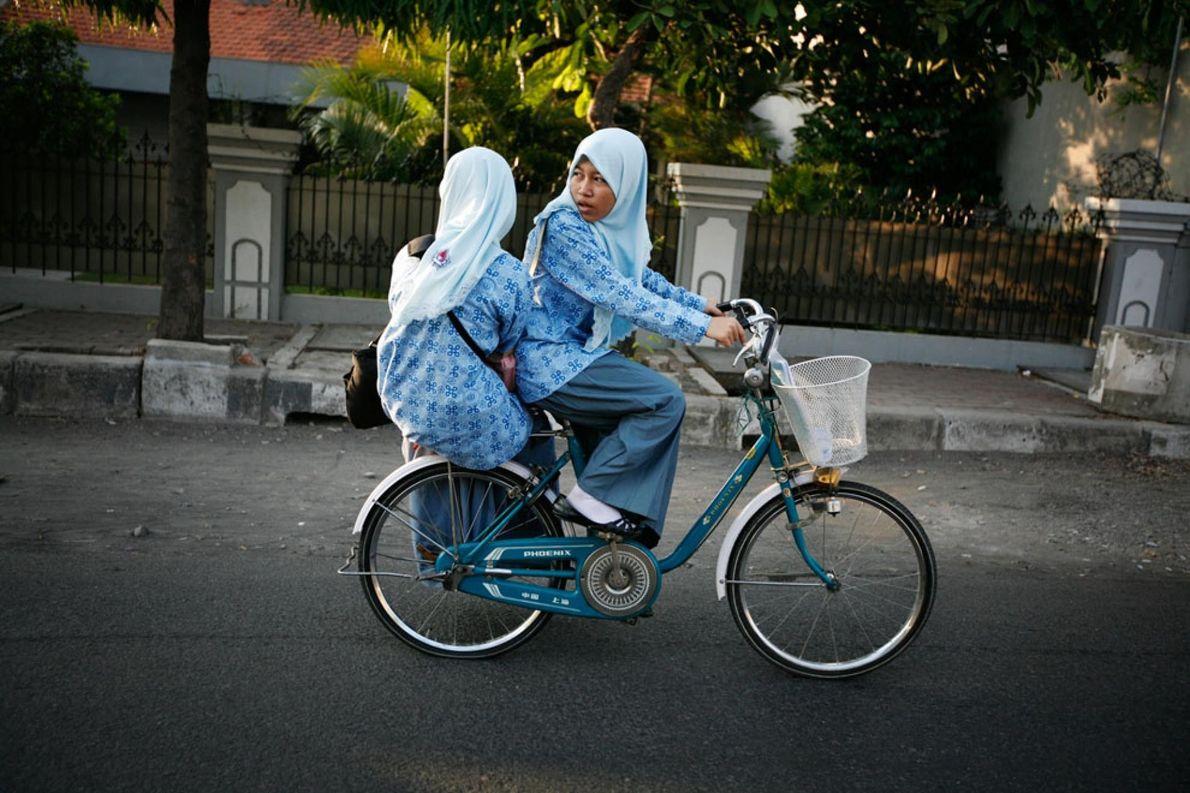 SURABAYA, INDONESIA Una joven colegiala musulmana e indonesia mira el tráfico que hay detrás de ella mientras ...