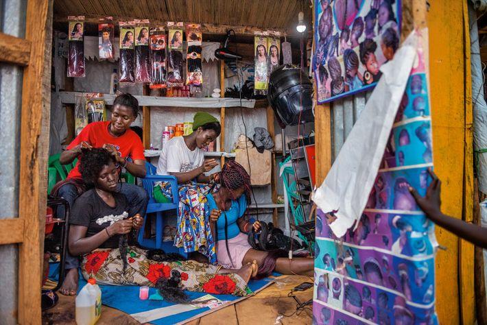 Knight Mai (izq.) y Florence Stima (dcha.), de Sudán del Sur, trabajan en un salón de ...