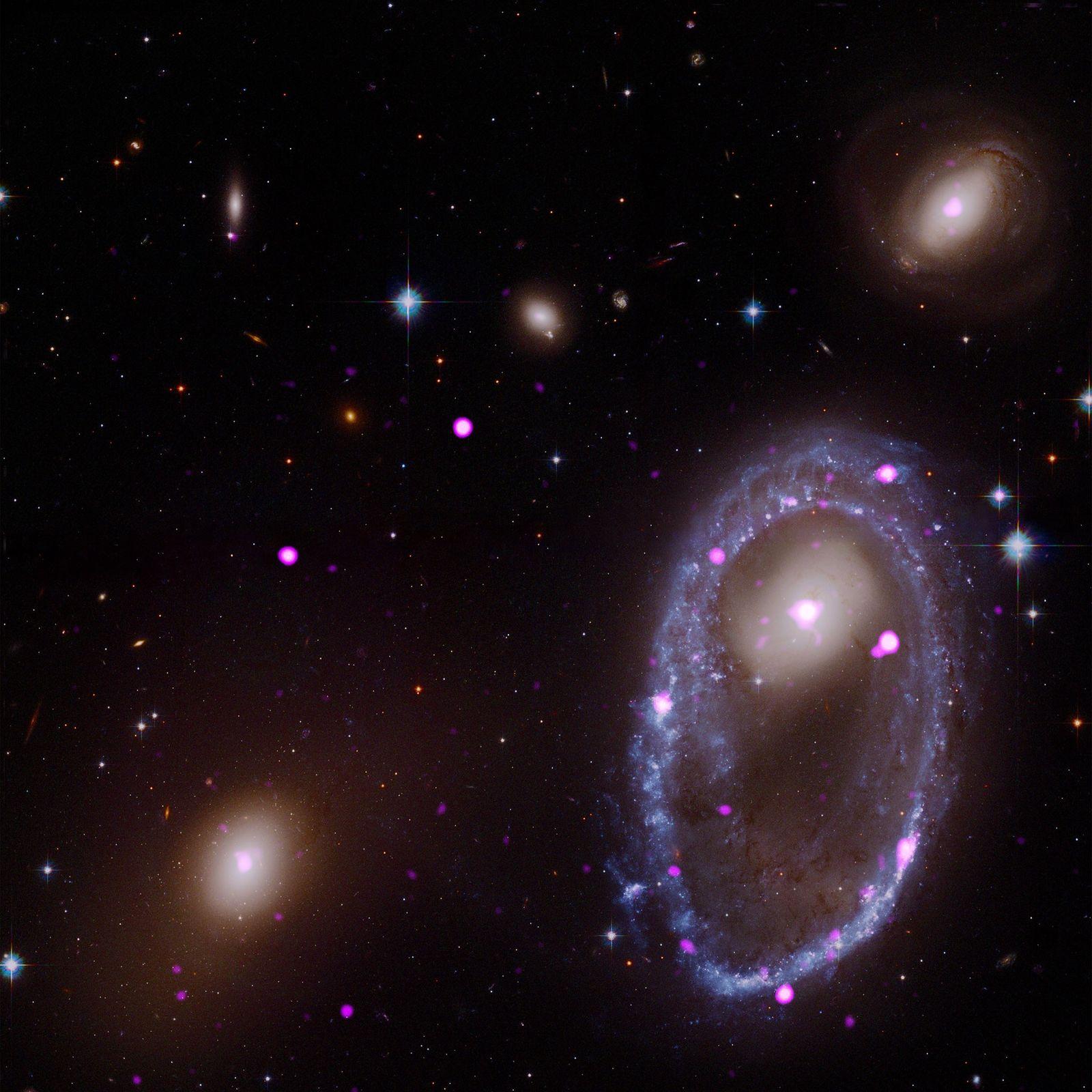 Una imagen compuesta desde los telescopios espaciales Hubble y Chandra muestra una galaxia anillo conocida como ...