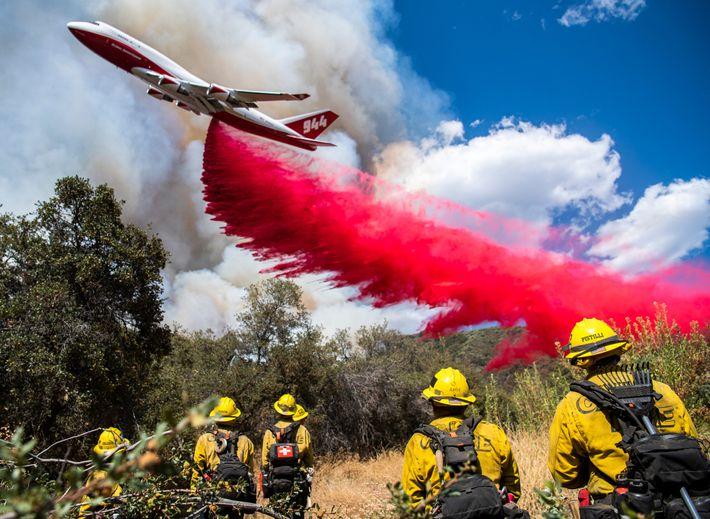 Un avión lanza retardante de llama para frenar la propagación del incendio de El Dorado.Durante el ...