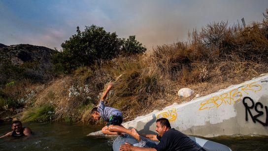 Eddie Lopez y su hijo, Eddie Jr., juegan cerca de una tubería de desagüe en el ...