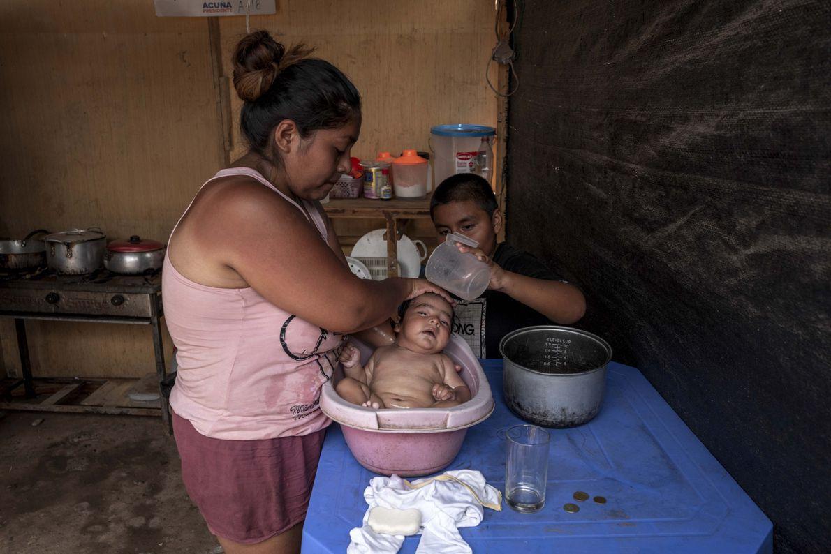 Sandra baña a su bebe con la ayuda de su hijo. Debido a que no cuentan ...