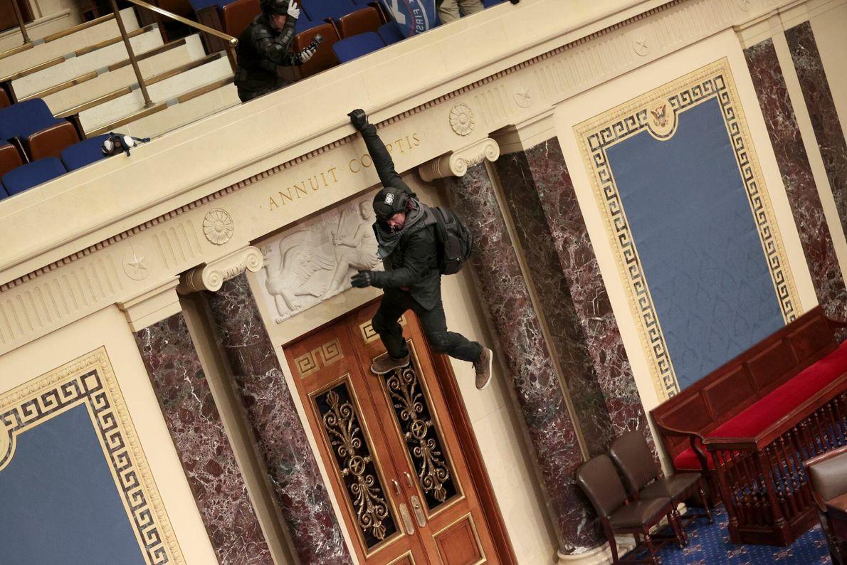 Un seguidor de Trump cuelga del palco de la Cámara del Senado.