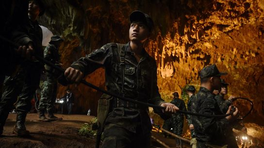 Los soldados tailandeses pasan un cable eléctrico en lo profundo de la cueva de Tham Luang ...