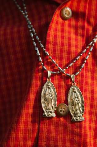 La imagen de la Virgen en dos collares que cuelgan del cuello de un joven hombre ...