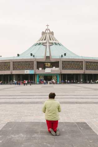 Una mujer se pone de rodillas frente a la basílica para mostrar su devoción ante las ...