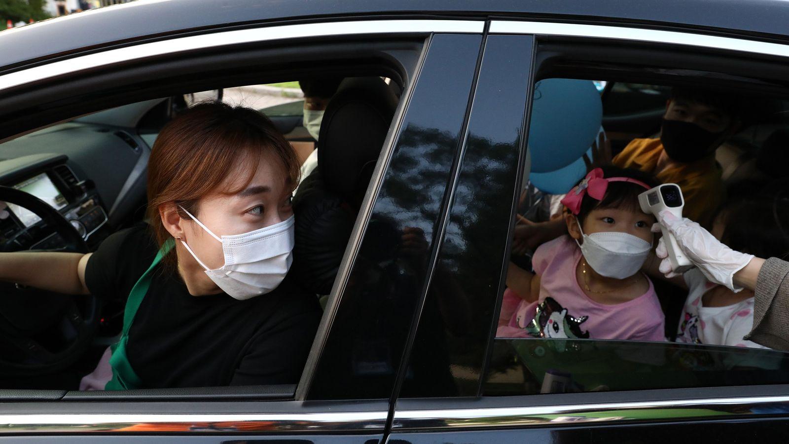 Una madre observa cómo le toman la temperatura a su hija en una clínica con modalidad ...