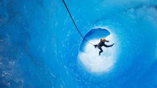 An ice climber moves through a glacial cave inside Torres del Paine National Park's Grey Glacier. ...