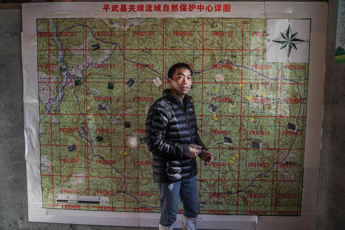 El guardabosques Meng Ji se para frente a un mapa de una reserva comunitaria que ahora ...