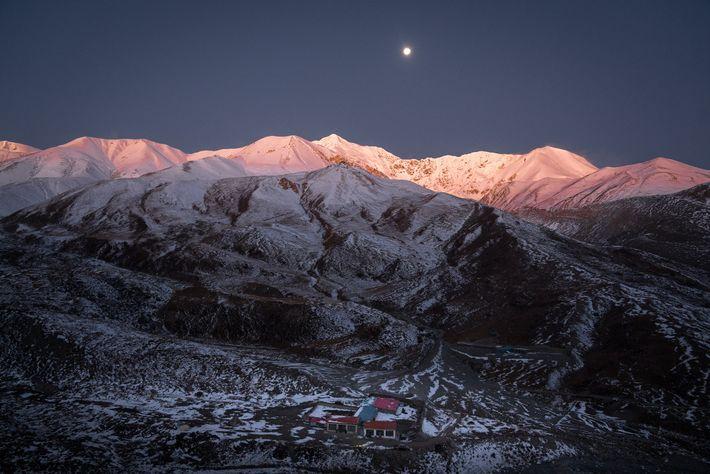 Una casa tibetana se encuentra en la base de las montañas en el Sanjiangyuan National Park, ...