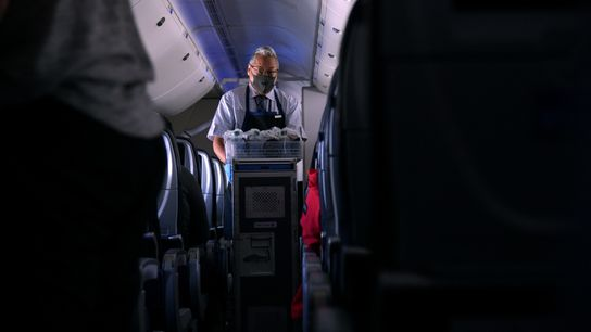 Un auxiliar de vuelo con mascarilla reparte refrigerios en un vuelo desde San Francisco, California, a ...