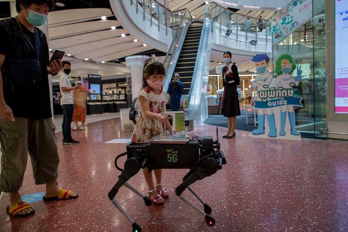 Una niña se desinfecta las manos con desinfectante dispensado por un robot que camina por Central ...