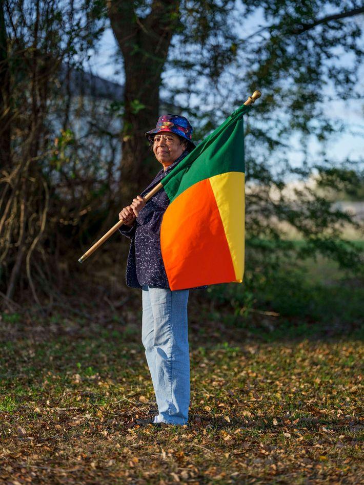 Patricia Frazier lleva la bandera de Benín, el país actual antes gobernado por el reino de ...