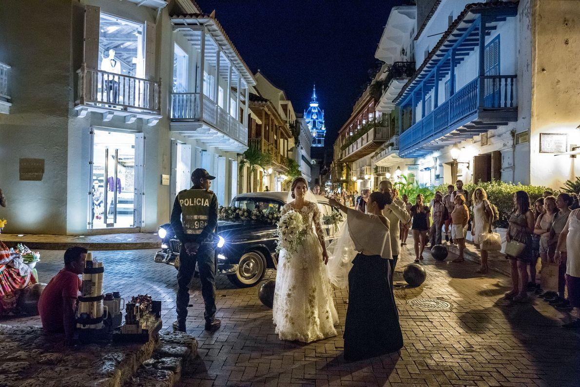 Peatones observan la llegada de una boda a la iglesia de San Pedro Claver, en el ...